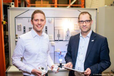 Smart Home-Systeme: Projektteam vor der Smart Home-Wand, mit der sie verschiedene Anwendungen erläutern (Bild: Costa Belibasakis | TH Köln).