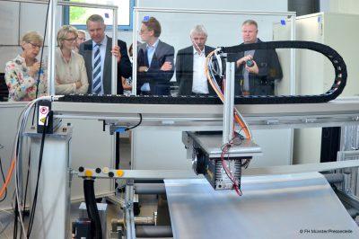Jürgen Gröninger (3.v.l) demonstriert Prof. Dr. Ute von Lojewski (l.) und Ministerin Anja Karliczek die Anlage zur Laserperforation der Folie (Bild: Pressestelle   FH Münster.)