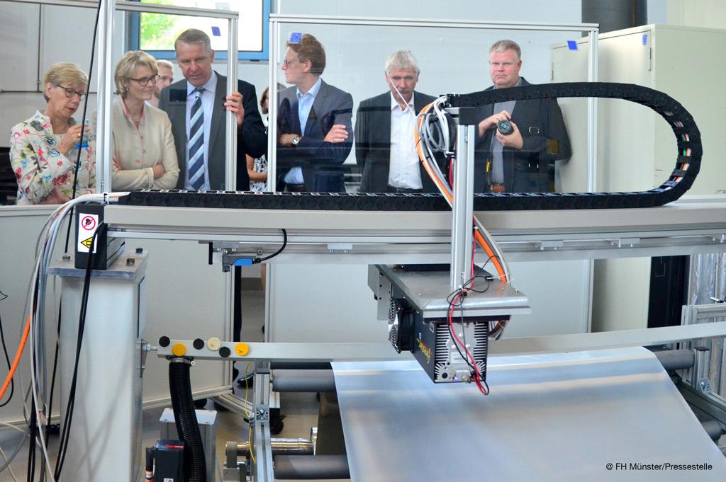 Jürgen Gröninger (3.v.l) demonstriert Prof. Dr. Ute von Lojewski (l.) und Ministerin Anja Karliczek die Anlage zur Laserperforation der Folie (Bild: Pressestelle | FH Münster.)