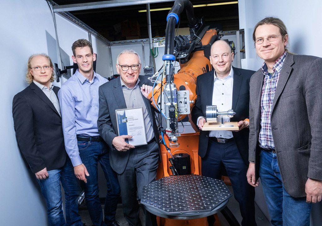Freuen sich über den MTU Supplier Award (v.l.): Projektmitarbeiter Victor Holstein und Hendrik Conze, Geschäftsführer Wolfgang Weber und Lorenz Vinke sowie Prof. Dr. Matthias Hermes (Bild: ALMECON | FH Südwestfalen).
