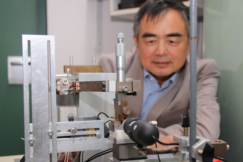 Prof. Dr. Jian Song sitzt vor einem Steckverbinder.