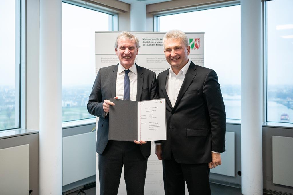 Professor Hubert Otten erhält den Förderbescheid aus den Händen von Wirtschaftsminister Professor Andreas Pinkwart. (Bild: Hochschule Niederrhein)