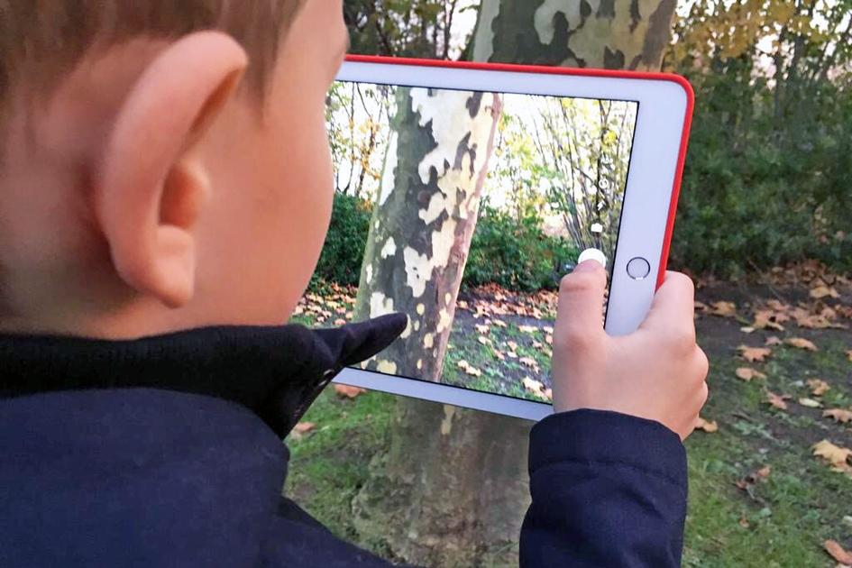 Bild eines Kindes, das ein Tablet in der Hand bedient.