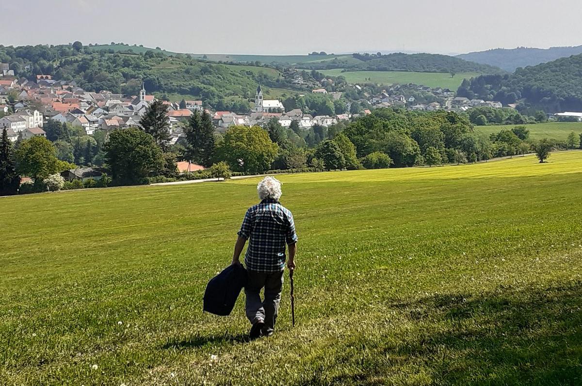 Mann geht mit Stock in der rechten und Jacke in der linken Hand über eine grüne Wiese. In Hintergrund ist ein Dorf zu sehen. (FH Münster | Katharina Kipp).