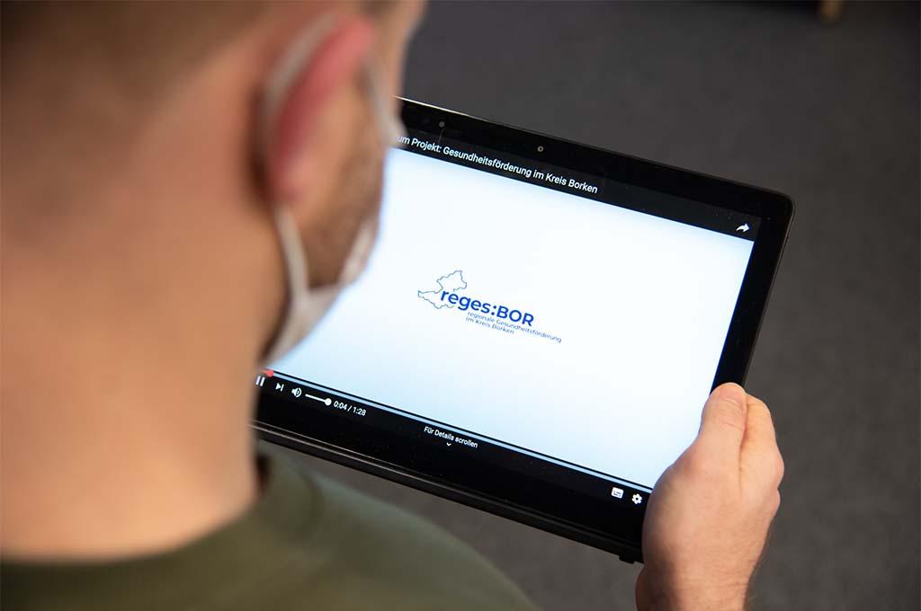 """Mann hält ein Tablet in der Hand, auf dem das Logo des Projektes """"reges:BOR"""" abgebildet ist."""