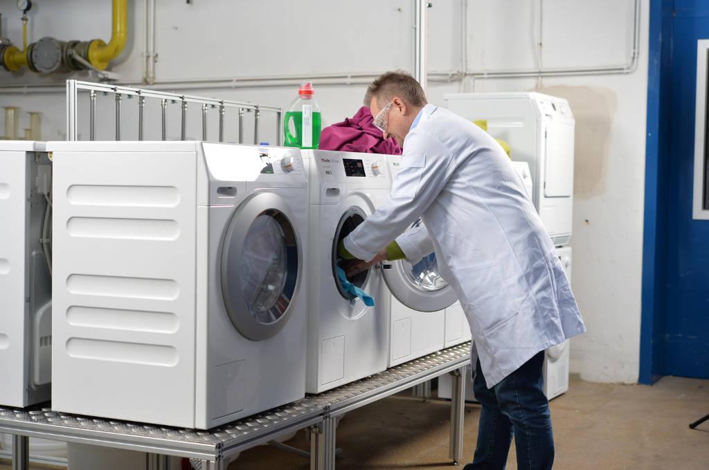 Stefan Brandt steht im Waschlabor der Hochschule Niederrhein vor einigen Waschmaschinen.