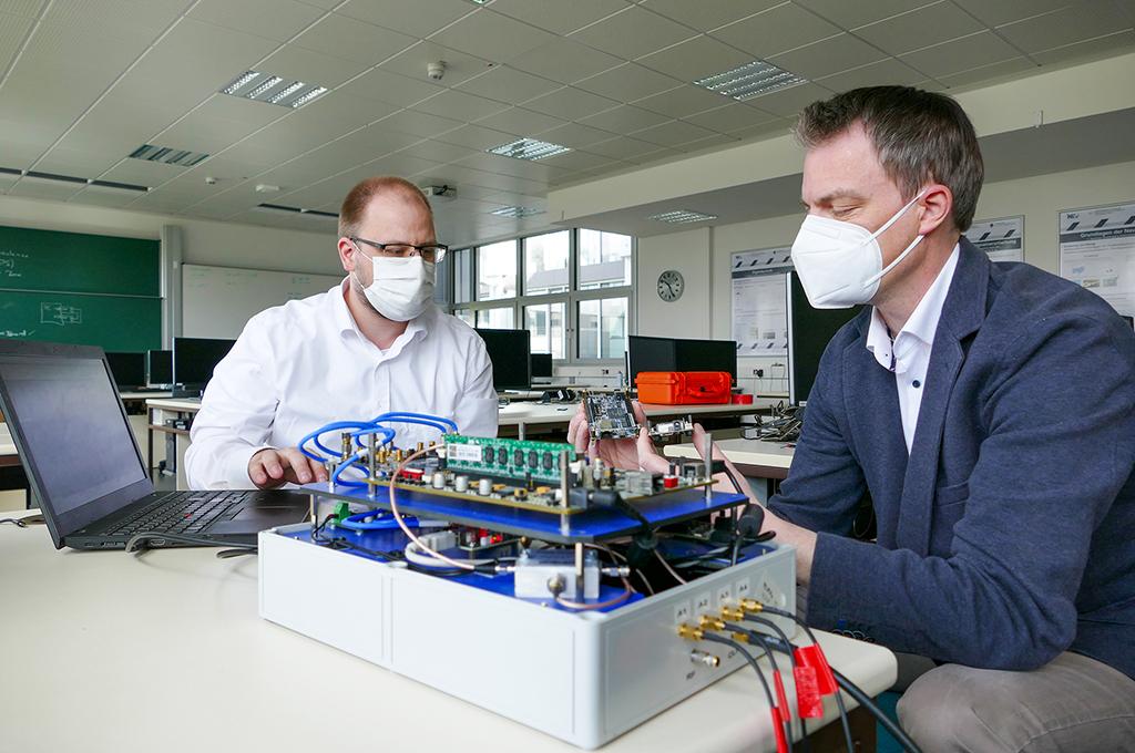Masterabsolvent Markus Biermann und Professor Kappen sitzen am Tisch und schauen auf ein technisches Gerät, das Biermann gebaut hat.