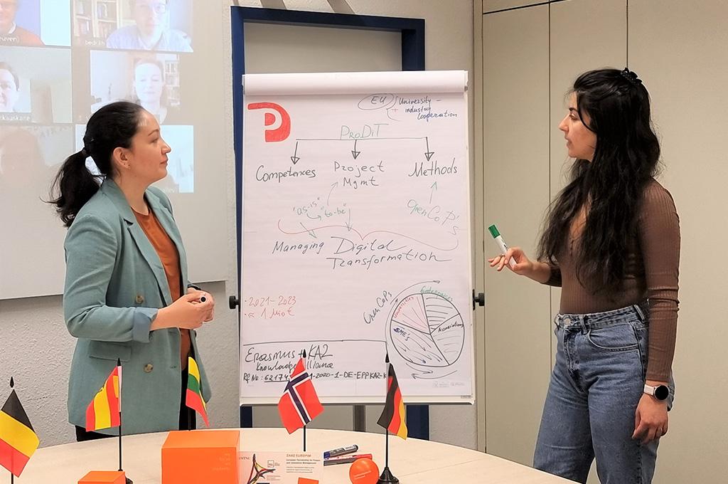 Anna Badasian und Nargiza Mikhridinova stehen vor einer Leinwand, die Informationen zu dem Projekt ProDiT enthält.