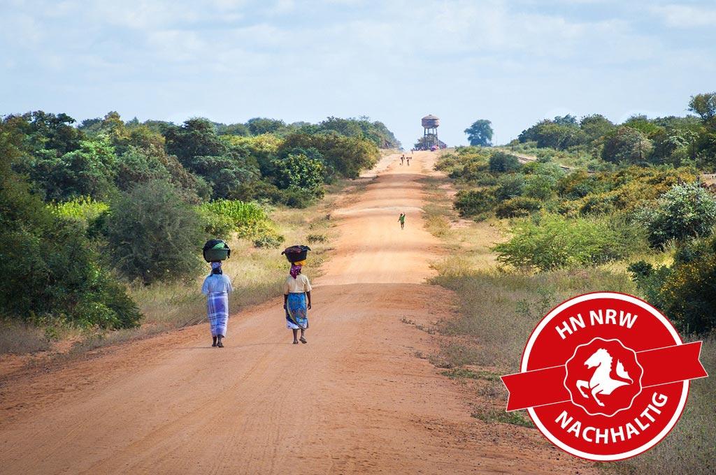 Zwei Menschen laufen staubigen Weg entlang