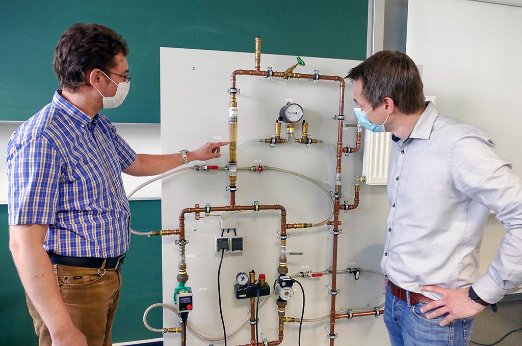 Zwei Männer stehen vor Pumpenleitungen