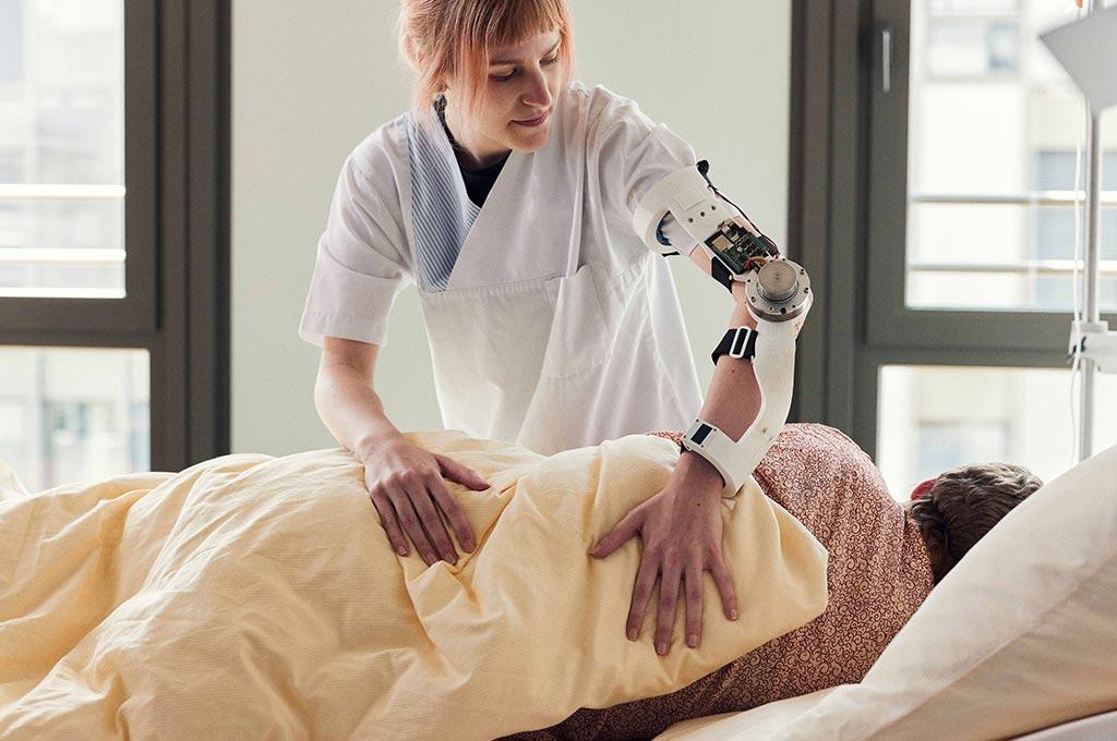 Pflegekraft arbeitet am Patientenbett mit Prototyp einer humanmechatronischen Orthese am Arm