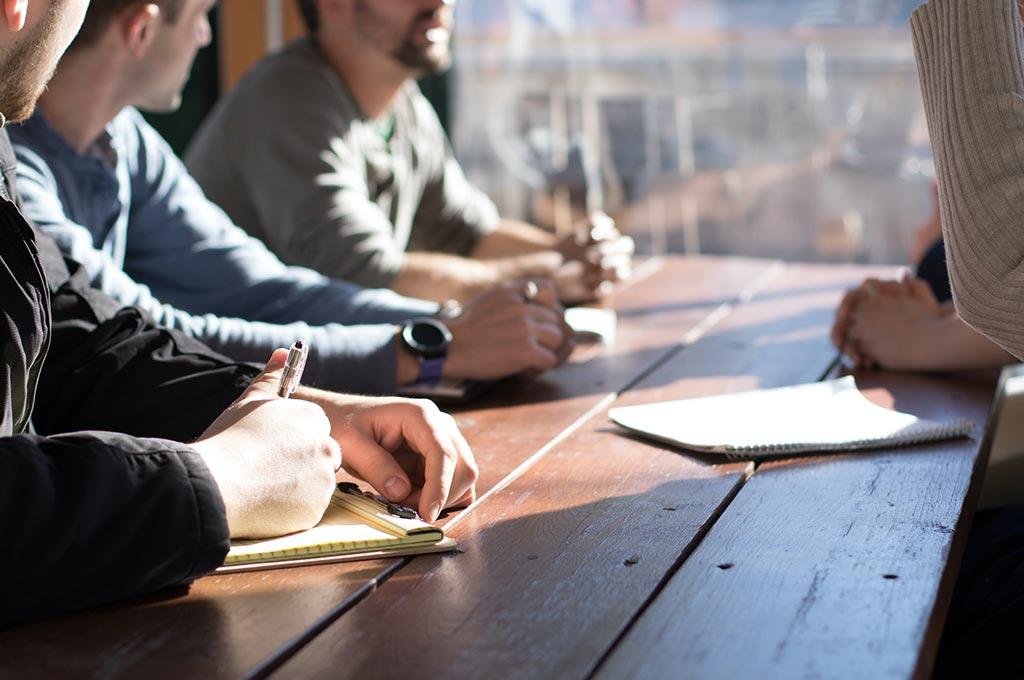 Menschen sitzen an einem Tisch