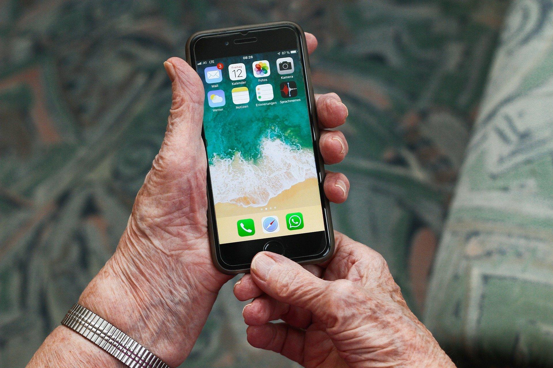 Zu sehen ist ein Smartphone, das von einer älteren Person in der Hand gehalten wird